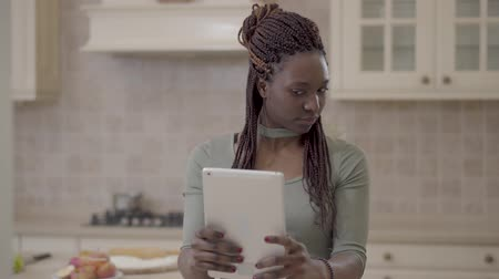 pigtail : Portrait of african american young woman making selfie on tablet on the background of modern kitchen Stock Footage