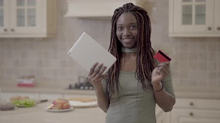 raszta : Portrait of beautiful african american smiling woman taking tablet and credit card after successful transaction on internet