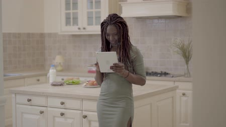 accepting : Pretty smiling african american woman with dreadlocks standing in the kitchen with tablet in hands. Lady did purchase and shows red credit card. Woman is happy and positive Stock Footage