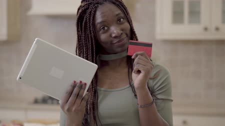 acquirente : Portrait cute smiling african american woman with dreadlocks standing in the kitchen with tablet in hands. Lady did purchase and shows red credit card. Woman is happy and positive