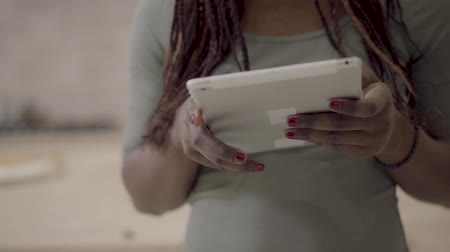 pigtail : African american young woman taking tablet in hands searching some information in internet or chatting. Close up Stock Footage