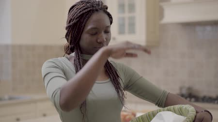 perverso : Attractive african american woman with dreadlocks working in the kitchen, she is tired and wipes her forehead with her hand. Lady opens wicker basket. Housewife life. Slow motion