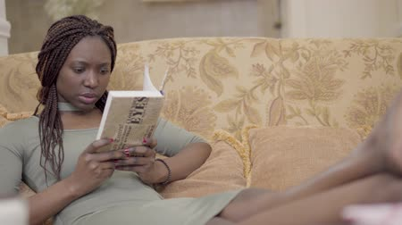 hazugság : Pretty concentrated african american woma nwith dreadlocks lying on the comfortable sofa couch reading the book with her bare feet up. Lady resting at home. Camera moves left