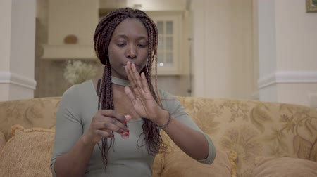 pigtail : Portrait of pretty african american woman making red polish manicure on the coach in modern living room Stock Footage