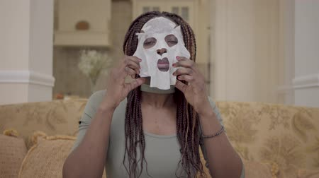 косички : Portrait of pretty african american woman putting moisturizing facial mask on her face on the coach in modern living room Стоковые видеозаписи