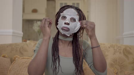 facecare : Portrait of cute beautiful african american woman putting moisturizing facial mask on her face on the coach in modern living room