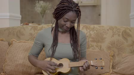 raszta : Portrait of pretty african american woman playing ukulele guitar on the coach in modern living room