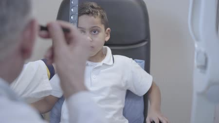 vision correction : Portrait of handsome mulatto boy sitting in the chair of doctor oculist. Professional ophthalmologist checks the eyesight of the child. Eye examination. Camera moves left behind doctor back Stock Footage