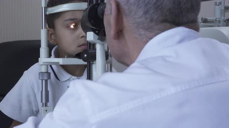 tıbbi bakım : Little handsome boy doe eye test at clinic sitting in front of doctor in white medical coat looking in eye test machine. Mature optometrist examining patient eye using light. Camera moves left