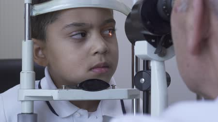 pediatria : Little handsome boy doe eye test at clinic sitting in front of doctor in white medical coat looking in eye test machine. Mature optometrist examining patient eye using light. Camera moves left