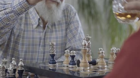 vecinos : Two old men drinking whiskey while playing a game of chess sitting at home on the leather sofa. Caucasian old men neighbors friends playing chess joyfully indoors. Leisure of the pensioners