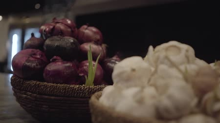 сосредоточиться на переднем плане : Close up view of sprouted purple onion and garlic lying in wicker basket on the table in restaurant kitchen. Camera moves. Focus changing from foreground to background