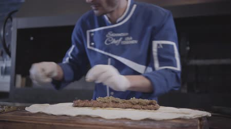 gürcü : Skillful man in blue chef uniform cooking lula kebab in modern restaurant. Cook puts topping on the grilled minced meat lying on pita lavash close up