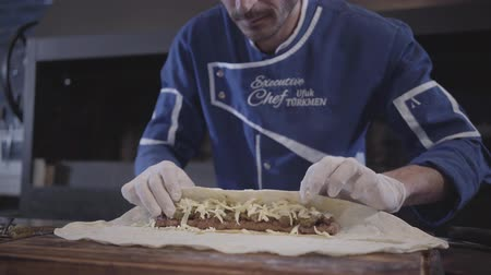 pita : Professional man in blue chef uniform cooking lula kebab in modern turkish restaurant. Cook putting cheese on the grilled minced meat and wrapping it in pita lavash close up