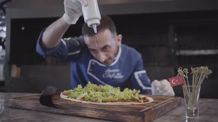 pita : Skillful man in cook uniform preparing tasty dish wrapped in lavash. Chef in white rubber gloves pouring lettuce leaves lying over pita with bbq sauce from bottle. Turkish cuisine