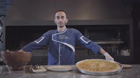 pita : Portrait of a confident successful chef in a blue uniform standing next to a delicious, appetizing dish in the kitchen.