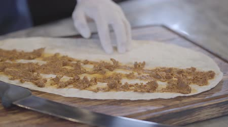 pita : Chef hand carefully spreading toppings over pita. Hands of man in rubber gloves preparing dish wrapped in lavash. Turkish cuisine
