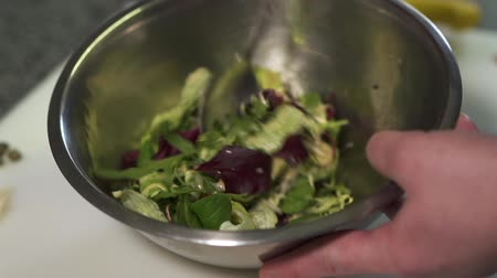 espinafre : Chef hands holding big aluminium bowl with salad poured with sauce. The man mixing tometoes, spinach, arugula, lettuce and basil leaves close up. Cook preparing food in the kitchen. Healthy lifestyle