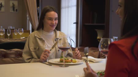 stories : Two positive girlfriends sitting in the modern restaurant, together. Girls talking chatting have conversation in the luxury restaurant. Friends have meeting in comfortable place Stock Footage