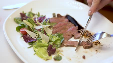 cielęcina : Thin slices of meat with salad on the plate. Hands with fork and spoon gently cut small piece of meat