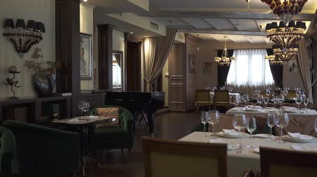 talher : Beautiful and richly served tables in the restaurant. A cozy decorated room. Luxury reception. stylish glasses, plates with napkins and silver cutlery on the tables. Camera moves right