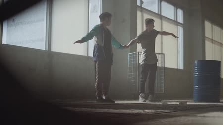simultaneously : Two men dancing in the dark and dusty room of abandoned building. Teenagers making dance move simultaneously, holding hands. Flexible men making wave with their bodies. Slow motion Stock Footage