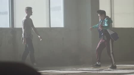 simultaneously : Two skilled dancers dancing in front of the large window in abandoned building. Teenagers making dance move simultaneously. Guys practicing in breakdance. Hip hop culture. Rehearsal. Contemporary.