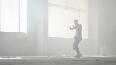 simultaneously : Skillful young great hip-hop dancer performing in the fog. Hip hop culture. Rehearsal. Contemporary.