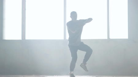 гимнастика : Confident young passionate hip-hop dancer performing in the fog. Hip hop culture. Rehearsal. Contemporary.