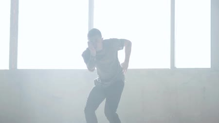 simultaneously : Confident young passionate hip-hop dancer performing in the fog. Hip hop culture. Rehearsal. Contemporary.