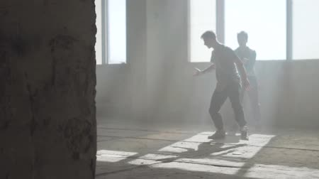 breakdancing : Two friends of successful dancers are dancing breakdance in an abandoned dusty building. Training skilled hip hopers. Contemporary. Hip hop culture. Rehearsal. Stock Footage