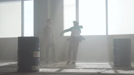 simultaneously : Dance battle of two street dancers in an abandoned building near the barrel. Hip hop culture. Rehearsal.