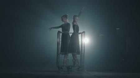 hangar : Two graceful professional ballet dancers dancing on her pointe ballet shoeses in spotlight on black background in studio. Ballerinas shows classic ballet pas standing in a metal trolley.