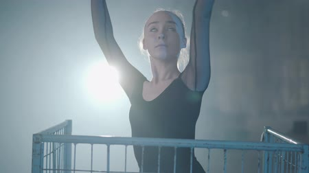 body building : Portrait of graceful professional ballerina dancing in black dress in the studio inside the blue cage in spotlight on a black background. Young beautiful woman raising hand standing in a metal trolley.
