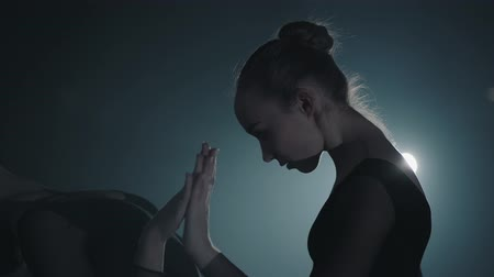 floodlight : Close up portrait two graceful professional ballerinas dancing elements of classical ballet in the dark. Ballet dancers shows classic ballet pas in spotlight on black background in studio. Stock Footage