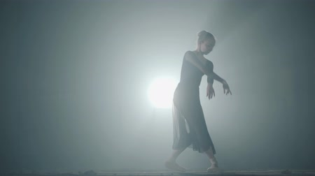 güzel sanatlar : Beautiful young ballerina in darkness. Ballet practice in black background. Young graceful ballerina dancing elements of classical ballet in the dark with light and smoke on the background. Stok Video