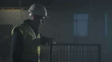 stavitel : Serious man in the builders uniform and helmet comes and puts his hand on the cage looking around the abandoned building. Portrait of thoughtful architect in empty room. Studio shot Dostupné videozáznamy