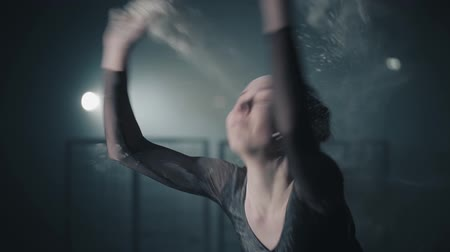 tüt : Portrait of professional ballerina dancing in black dress in the studio in spotlight on black background. Young beautiful ballet dancer arching body back and throwing flour. Slow motion.