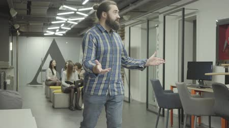 compensar : Bearded man studying papers in the office. Young colleague riding the bike in the office and pushes bearded guy in the shoulder, papers fall down. Bike rider apologizing and collecting documents