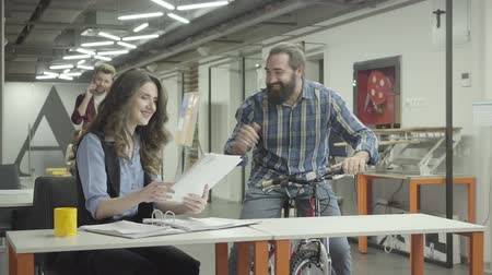 internar : Pretty woman and handsome bearded man communicate in the office, laughing. Beardie emotionally discussing information with a lady, holding his bike. Colleagues smiling and positive. Workplace.