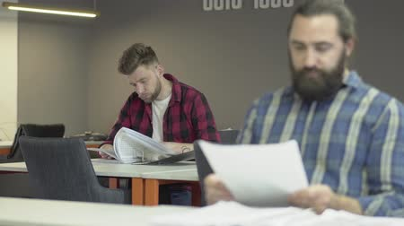 めい想的な : Two bearded office workers work in the office studying the reporting documentation. Colleagues read papers with work plans. One office worker or businessman is indignant at bad pokachateley and shouts