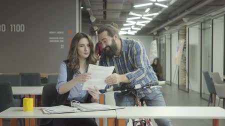 beardie : Bearded smiling positive man rides his bike closer with papers in hand and shows documents to the lady in the office. Pretty woman and bearded man communicate in the office, discussing new document
