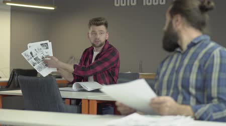 スプレッド : Two colleagues sitting in office studying new working information from papers. Young man in the background asking advice of bearded older co-worker but he spreads his arms to the side