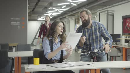 beardie : Bearded smiling man rides his bike with papers in hand and shows documents to the lady in the office. Pretty woman and bearded man communicate in the office, discussing new document, they are excited Stock Footage