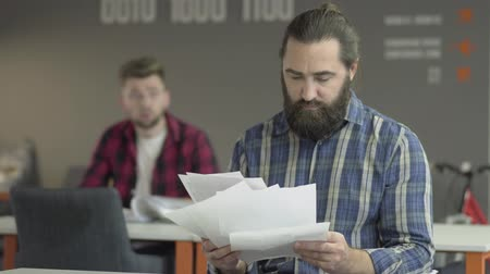 umma : Angry bearded man sitting in the foreground studying papers in the office. Worker turns back to his colleague and throw papers to his table, then stands up and walks away. Problem in working process Stok Video