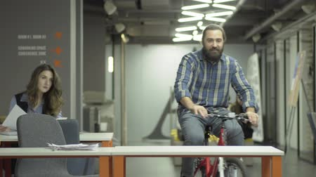 chegar : Bearded smiling man rides his bike in the modern office. Rider says hello to his female colleague and sits at his workplace. Office worker arrived at work on the bike. Man starts his working day