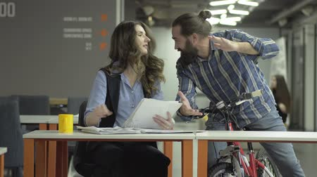 beardie : Joyful colleagues chatting in the workplace. Successful office workers share the news. Bearded man on a bicycle and beautiful business woman with papers. Stock Footage
