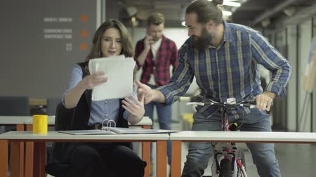 beardie : Successful office workers share the news. Bearded man on a bicycle and beautiful business woman with papers. Joyful colleagues chatting in the workplace.