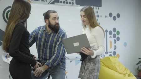 beardie : Two pretty women standing and communicating in the office. Bearded man on his bike riding closer and gives papers to them, then moves away. Ladies laughing at the strange guy. Active working life