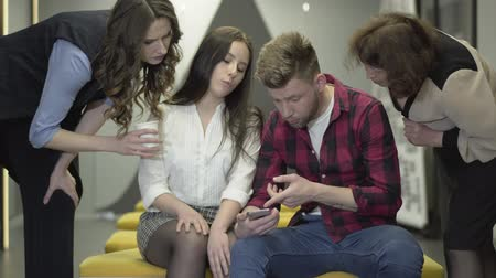 стремление : Young man in casual clothes sitting near pretty female colleague showing her pictures on his cell phone, both are shocked. Female co-workers to join them and look on the screen, discussing the subject Стоковые видеозаписи